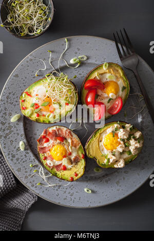 eggs baked in avocado with bacon, cheese, tomato and alfalfa sprouts - Stock Photo
