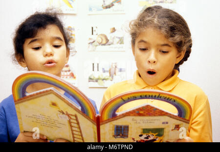 Two little girls reading out loud from french book on colours - Stock Photo