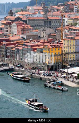 Douro River cruise boat with tourists passing Cais da Ribeira promenade and square, Porto, Norte Region, Portugal - Stock Photo