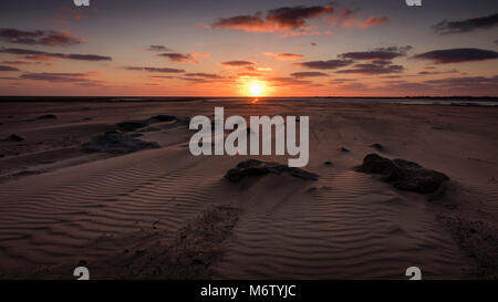 Sand covered rocks at Cleethorpes beach as the sun rises over the horizon. - Stock Photo