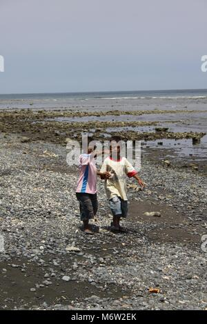 Beautiful quiet beaches in the northwest of Bali Children walking ashore - Stock Photo