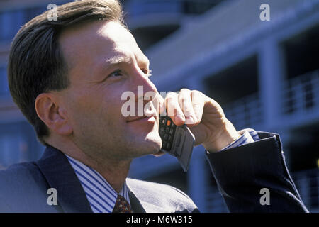 1995 HISTORICAL CAUCASIAN BUSINESS MAN WITH MOBILE CELLULAR TELEPHONE (©MOTOROLA CORP 1995) OUTDOORS - Stock Photo