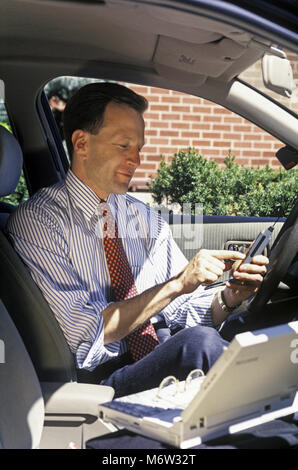 1995 HISTORICAL CAUCASIAN BUSINESS SALES MAN WITH CELLULAR TELEPHONE (©MOTOROLA CORP 1995) IN MOBILE AUTOMOBILE - Stock Photo