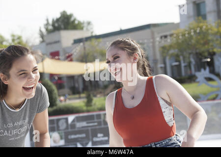 Two teen girl friends goofing off on an outdoor ice rink in Southern California - Stock Photo