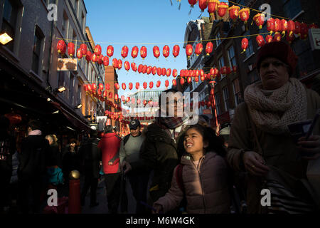 Bright red and yellow lanterns are strung across between the buildings creating a canopy of colour for Chinese New - Stock Photo