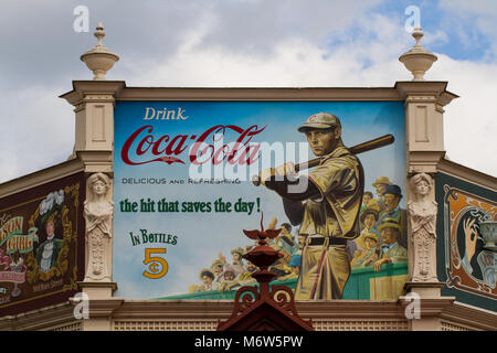A large billboard with an old fashioned, vintage Coca Cola advertisement showing a baseball Star and Coke slogan. - Stock Photo