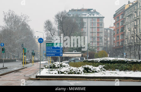 Road signs in Milan, Lombardy, Italy pointing to various landmarks including San Siro stadium and Linate Airport. - Stock Photo