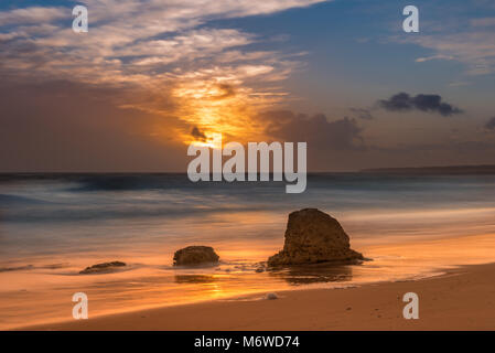 Long Exposure at Sunset on Praia do Galé, Albufeira, Portugal with a distant storm clearing - Stock Photo