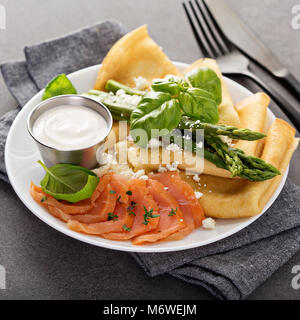 Savory crepes with salmon, sour cream, feta and asparagus - Stock Photo