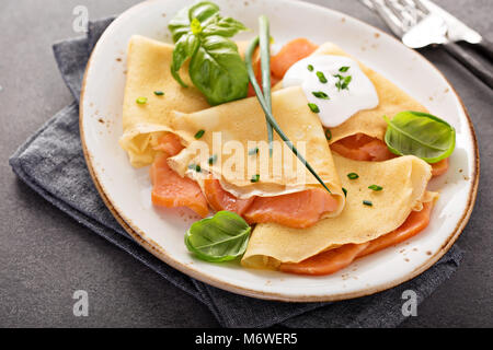 Savory crepes with salmon filling and sour cream - Stock Photo
