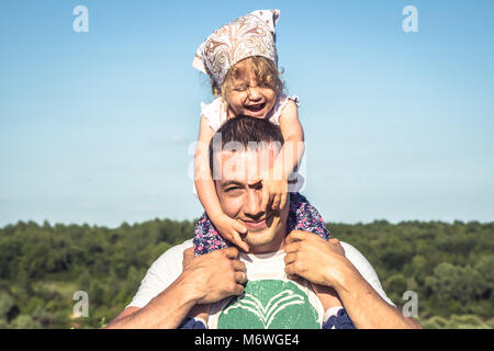 Father cute daughter having fun together as family lifestyle portrait in front of  blue sky. Happy father holding - Stock Photo