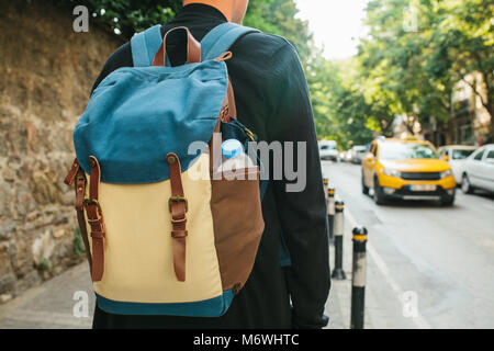 Young male tourist with a backpack in the big city is waiting for a taxi. Journey. Sightseeing. - Stock Photo