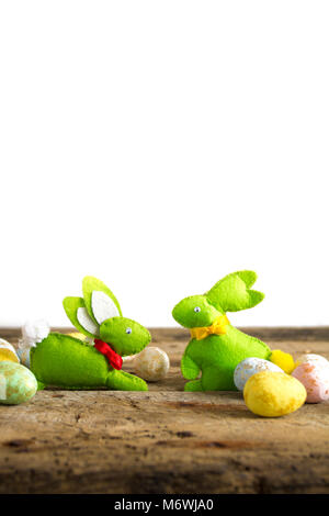 Easter handmade rabbits on wooden table with eggs isolated on white. - Stock Photo