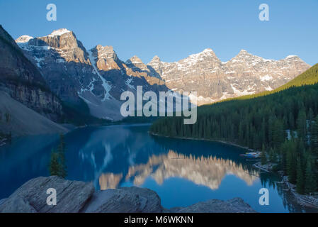 Afternoon light  on the snowy peaks surrounding the stunning Moraine Lake, Alberta, Canada. The mountains are reflected - Stock Photo