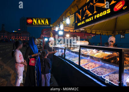 Horizontal view of people buying takeaway from a fastfood stall on Galle Face Green in Colombo, Sri Lanka - Stock Photo