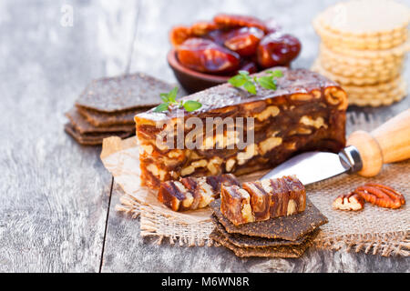 Date  walnut wedge with multigrain crackers on wooden table - Stock Photo