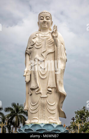 Standing Buddha statue at the Vinh Trang Temple in Mytho City, Mekong Delta, Vietnam - Stock Photo