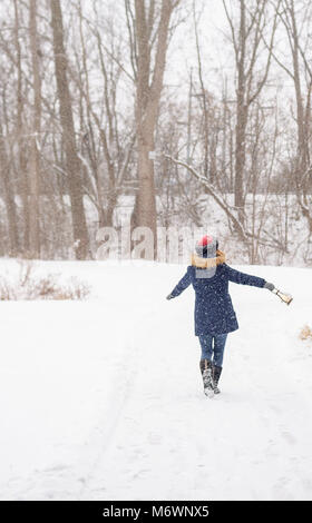 woman dancing and swinging arms in winter wonderland in forest with snow falling - Stock Photo