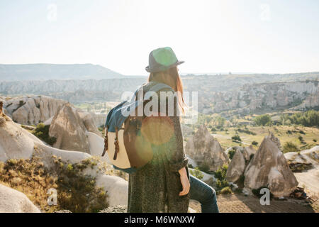 A traveler in a hat with a backpack stands on a mountain and looks at a beautiful view in Cappadocia in Turkey. - Stock Photo