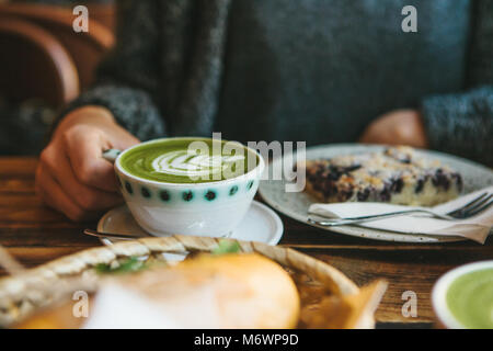The girl sitting in cafe and holding mug with green tea with milk next to piece of sweet pie and two sandwiches - Stock Photo
