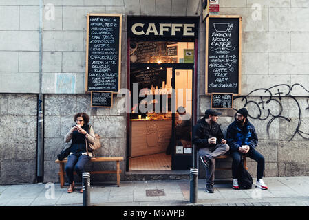 Madrid, Spain - November 3, 2017: People drinking coffee outside hipster cafe in Malasaña district in Madrid. - Stock Photo
