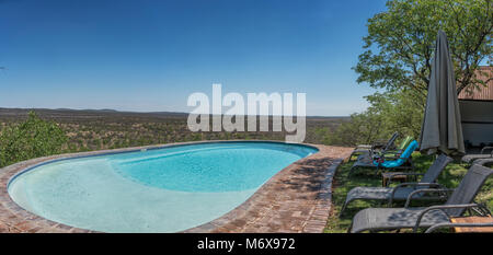 Pool with chairs overlooking the Namibian African savannah. - Stock Photo