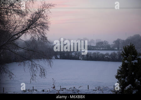 A winter view at sunrise over snow covered fields in rural Worcestershire England UK - Stock Photo