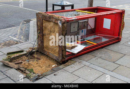 a vandalised or broken telephone box that has fallen over onto it's side in London. damaged call box toppled over - Stock Photo