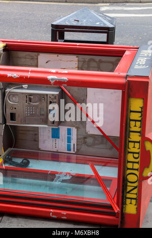 An old style red telephone coin operated card phone call box on it's side fallen over at the side of a london street. - Stock Photo