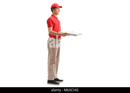 Full length profile shot of a teenage delivery boy holding a pizza box isolated on white background - Stock Photo