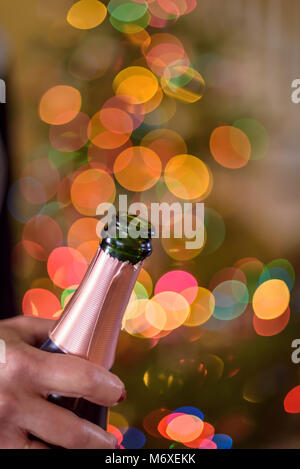 closeup of a woman holding a champagne bottle in front of bokeh Christmas lights on New Years Eve - Stock Photo