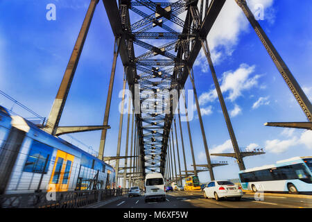 Public transportation and private passenger cars during intense traffic rush hour driving over Sydney harbour bridge - Stock Photo