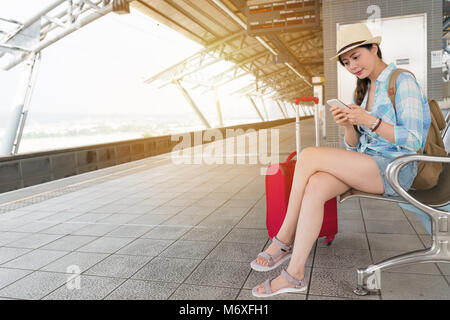 beautiful travel young woman sitting at bench texting message with smartphone. girl take train vacation with her - Stock Photo