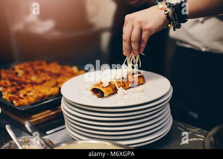 Woman preparing delicious mexican enchiladas. Culinary workshops - Stock Photo