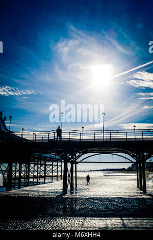 Cleethorpes pier silhouetted at sunrise in winter. Cleethorpes, North East Lincolnshire, England, UK - Stock Photo