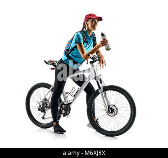 Cyclist in blue t-shirt with bicycle drinking a water in silhouette on white background. Sport and healthy lifestyle - Stock Photo