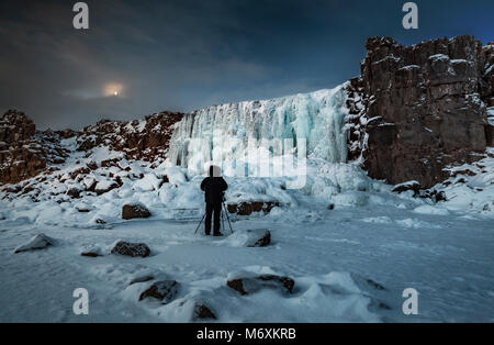 Photographer taking pictures by the frozen Oxararfoss Waterfall, Thingvellir National Park, Iceland. Unesco World - Stock Photo