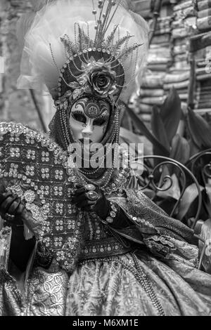 Woman holding fan and wearing feathered mask and ornate costume photographed in monochrome during Venice Carnival - Stock Photo