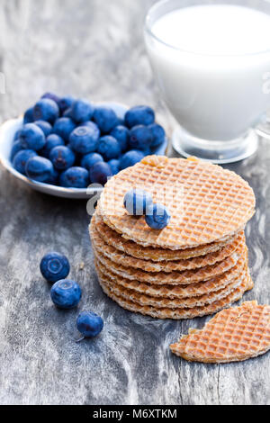 Stack  of Dutch caramel waffles with blueberry and cup of milk - Stock Photo