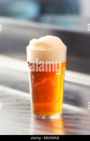 Freshly served pint of frothy draft beer with a good head in a glass on a metal bar counter in a close up side view - Stock Photo