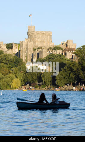 Two girls in a rowing boat on the River Thames with Windsor Castle in the background, England. April 2007. - Stock Photo