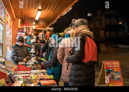 Karpacz, Poland -  February 2018 : People walking by and looking at the bookstore display in winter - Stock Photo