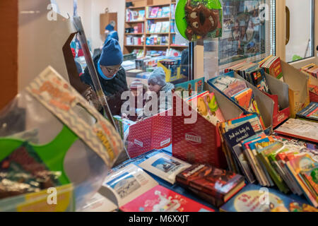Karpacz, Poland -  February 2018 : Mother with children inside a bookstore browsing through the variety of books - Stock Photo