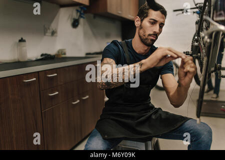 Man working on a bicycle in a repair shop. Worker fixing a bicycle brake wire in workshop. - Stock Photo