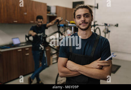 Worker standing with folded arms holding a spanner in workshop. Mechanics  assembling bicycles in repair shop. - Stock Photo