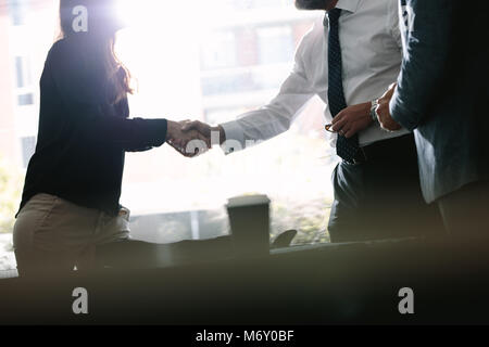 Business associates shaking hands after a deal in meeting. Business people hand shake and greeting each other after - Stock Photo