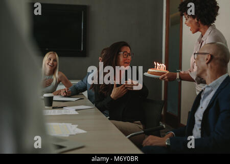 Office workers celebrating birthday of cheerful female colleague with cake in conference room. Coworkers congratulating - Stock Photo