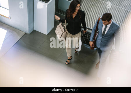 Business people arriving at hotel with luggage. Business people with luggage walking together and chatting. - Stock Photo