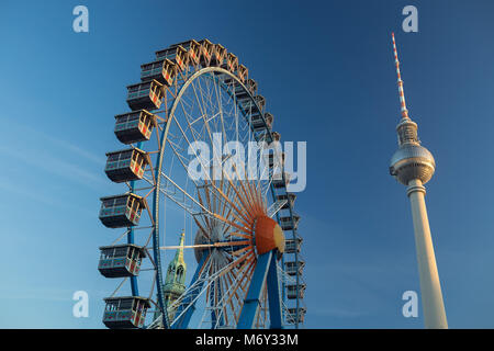 A ferris wheel at Neptunbrunnen with the Fernsehturm (TV Tower) in Alexanderplatz behind, Mitte, Berlin, Germany - Stock Photo