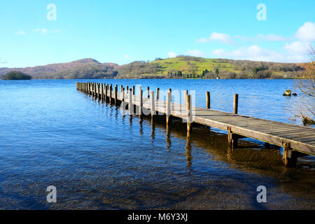 Long straight symetrical wooden foot jetty jutting out over a calm blue lake, with hills of green fields and forest - Stock Photo